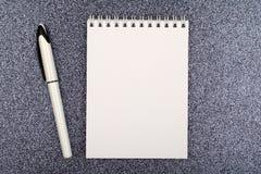 Biały ślimakowaty notatnik z piórem na czerni zdjęcia stock