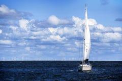 Biały żeglowanie jacht na błękitnym morzu przeciw niebu z chmurami, Obrazy Royalty Free