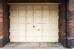 Biały antyka żelaza drzwi z kędziorkiem na czerwonym ściana z cegieł tle obrazy stock