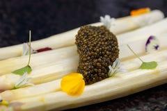 Biały asparagus słuzyć z kawiorem dekorującym z kwiatami na czarnym talerzu zdjęcie royalty free