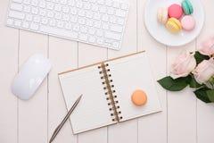 Biały biurko z kolorowymi macaroons, klawiaturą i otwartym notatnikiem, fotografia stock