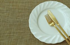 Biały Ceramiczny talerza, mosiądza Cutlery na Beżowej lunch macie z Bezpłatną przestrzenią dla i zdjęcia royalty free