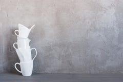 Biały crockery na stole przeciw textured popielatej ścianie zdjęcia royalty free