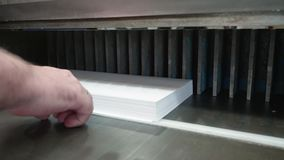 Biały człowiek przystosowywa paczkę biały papier w gilotyna krajaczu przed ciąć zbiory wideo