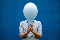 Biały człowiek zakrywa jego twarz z błękitnym balonem Fotografia Royalty Free