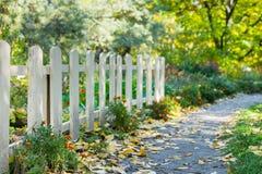 Biały drewniany ogrodzenie w parku wśród drzew, kwiatów i krzaków, Obraz Stock