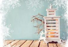 Biały drewniany rocznika lampion z płonącą świeczką, drewnianym rogaczem, boże narodzenie prezentami i gałąź na drewnianym stole, zdjęcie stock