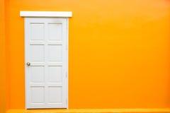 Biały drzwiowy klasyczny rocznik na kolor pomarańcze ścianie Zdjęcia Stock