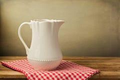 Biały dzbanek na tablecloth Zdjęcie Stock