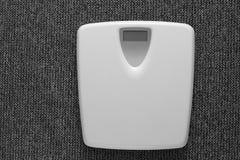 Biały elektroniczny waży na popielatego dywanowego tła czarny i biały monochromu Zdjęcie Stock