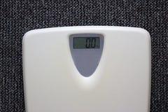 Biały elektroniczny waży z liczbą zero kg na popielatym dywanowym tle Obraz Royalty Free