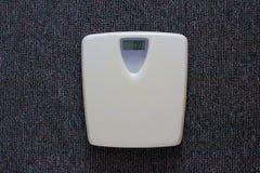 Biały elektroniczny waży z liczbą zero kg na popielatym dywanowym tle Zdjęcia Stock