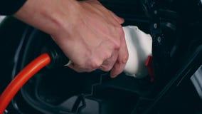 Biały elektryczny nozzle dostaje kładzenie w czarnego samochód zdjęcie wideo