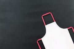 Biały fartuch na czarnej chalkboard teksturze fotografia royalty free