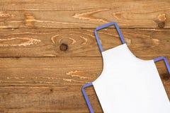 Biały fartuch przeciw starej drewnianej teksturze fotografia royalty free