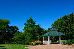 Biały Gazebo z zieleni Dachowej i Czerwonej cegły patiem w parku dalej Zdjęcia Stock
