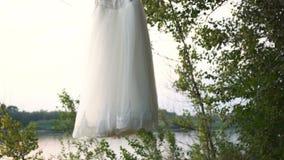 Biały handmade przypadkowy ślubnej sukni zrozumienie na gałąź w ogródzie zdjęcie wideo
