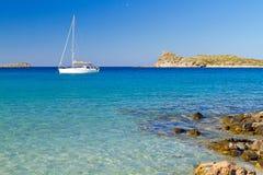 Biały jacht na idyllicznej plażowej lagunie Crete obrazy royalty free