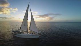 Biały jacht z ogromnymi białymi żeglarzami jest dryfujący wzdłuż spokojnej wody ocean, ludzie ogląda świt gdy słońce wzrasta Zdjęcie Royalty Free