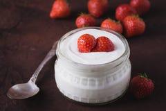 Biały jogurt w szklanym pucharze z łyżką i starwberries na nieociosanym tle Zdjęcia Stock