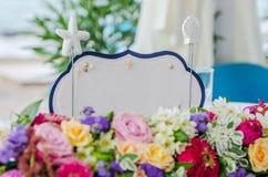 Biały karciany Właśnie zamężny znak na stole z kwiatami przy ślubem Fotografia Stock