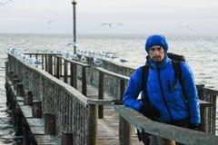 Biały Kaukaski męski podróżnik w sporty niebieska marynarka, rękawiczki, kapelusz, szkła i plecak pozycja na molu Atlantycki Oc, zdjęcia royalty free