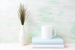 Biały kawowego kubka mockup z ciemną łąkową trawą w wazie i książkach Obraz Royalty Free