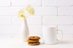 Biały kawowego kubka mockup z miękką żółtą orchideą w wazie i kucharzie Obrazy Royalty Free