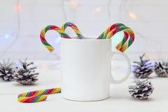 Biały kawowy kubek z Bożenarodzeniowymi cukierek trzcinami, rożkami i Przestrzeń dla Zdjęcie Stock