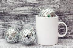 Biały kawowy kubek z Bożenarodzeniowymi dekoracjami - lustrzane piłki Zdrój Zdjęcia Stock