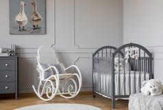 Biały kołysa krzesło z poduszką obok drewnianej kołyski w eleganckim dziecko pokoju z kaczka plakatem na ścianie zdjęcia stock