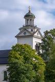 Biały kościelny wierza z bujny zieleni drzewami w świetle słonecznym fotografia stock