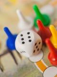 Biały kostka do gry sześcian blisko stubarwnego kontuaru na gry polu Obraz Royalty Free