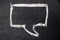 Biały kredowy rysunek jako bąbel mowa na czerni deski tle Fotografia Stock