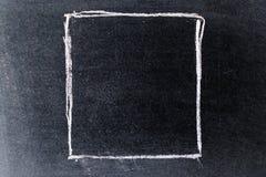Bia?y kredowy rysunek w puste miejsce kwadrata kszta?cie na czerni desce zdjęcie royalty free