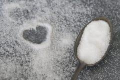 Biały krystaliczny cukier na ciemnej rocznik łyżce, hearth kształt na ciemnym kuchennym dresser fotografia royalty free