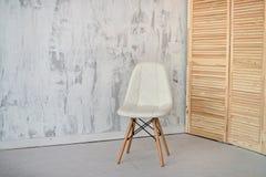 Biały krzesło na tle białego grunge ścienni i drewniani drzwi fotografia stock