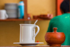Biały kubek i drewniany puchar przy stołem na cukiernianym tle Obrazy Stock