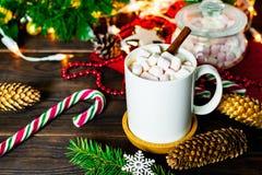Biały kubek kakao z marshmallows, lizakami, jedlinowymi rożkami, choinki gałąź, girlandą i płatek śniegu na drewnianym stole, obraz stock