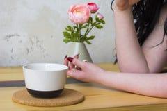 Biały kubek na drewnianym stojaku, żeńska ręka Fotografia Royalty Free