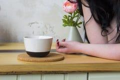 Biały kubek na drewnianym stojaku, żeńska ręka Fotografia Stock