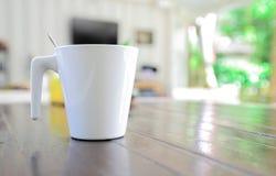 Biały kubek z łyżką na stole zdjęcia stock