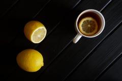 Biały kubek z czarną herbatą i plasterek cytryna stojaki obok owoc na ciemnej drewnianej powierzchni na widok minimalista obraz stock