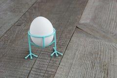 Biały kurczaka jajko w błękitnym śmiesznym stojaku na drewnianym tle Wielkanocny wystrój Obraz Royalty Free
