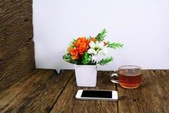 biały mądrze telefon na drewno stole z filiżanką herbata Fotografia Stock