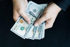 Biały młody człowiek liczy pieniądze, sto nowych dolarowych rachunków na czarnym tła zakończenia planie Obraz Royalty Free