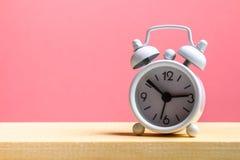 Biały mały budzik na drewnianej półce na różowym pastelowym tle minimalista obraz royalty free
