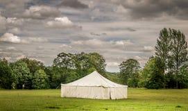 Biały markiza namiot w polu z podeszczowymi chmurami zdjęcie royalty free