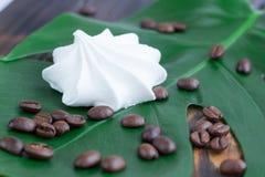 Biały marshmellow, kawowe fasole na zielonym liściu i drewniany backgro, Fotografia Royalty Free