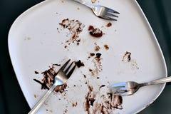 Bia?y matte prostok?tny talerz pusty i pobrudzony z resztkami czekoladowy tort i kruszki zdjęcie stock